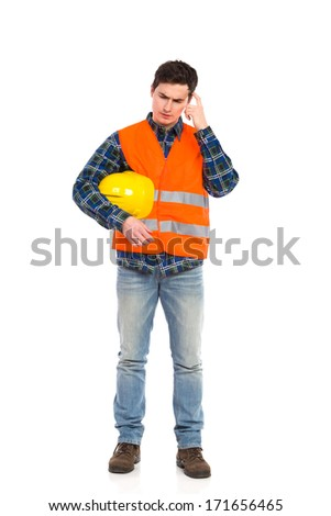 Construction worker in yellow helmet and orange waistcoat scratching head. Full length studio shot isolated on white.