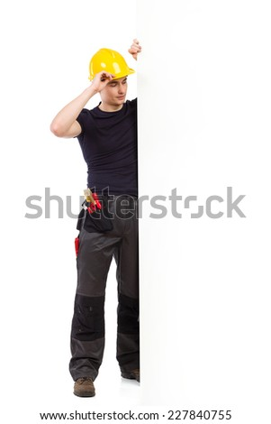 Construction worker in yellow helmet standing behind big banner, peeking and reading.  Full length studio shot isolated on white. - stock photo