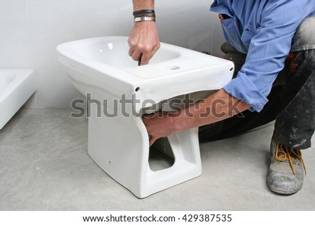 Construction worker installing a bidet in a bathroom.