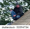 construction worker installing a skylight on house roof - stock photo