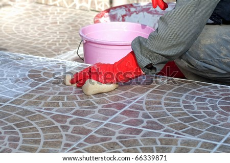 construction worker installing decorative tiles - stock photo