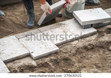 Construction worker installing the pavestone on the road  - stock photo