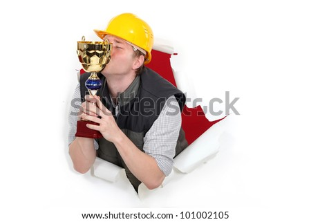 Construction worker kissing a trophy - stock photo