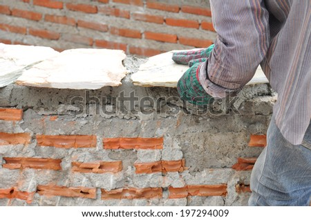 Construction worker laying  stone plates on brick wall with mortar - stock photo