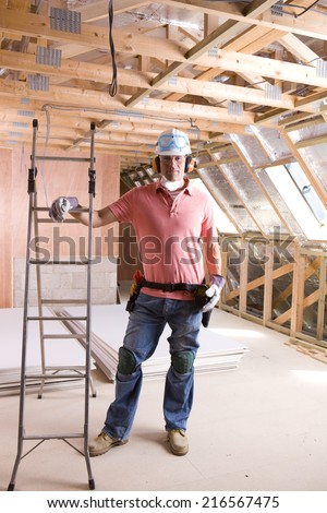 Construction worker leaning on ladder in attic - stock photo