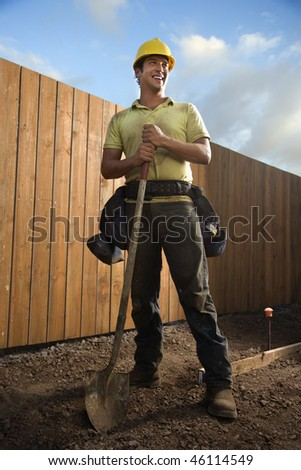 Construction worker leans on a spade and smiles to the side at a construction site. Vertical shot. - stock photo