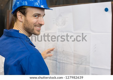 Construction worker looking at blueprint