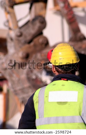 Construction worker looking over a building site, blank logo space on safety vest for addition of company identity - stock photo