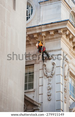 Construction worker lowers himself into position to perform maintenance high up of a building in London while using safety equipment and providing job security - stock photo