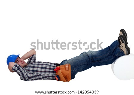 Construction worker lying down with his feet up - stock photo