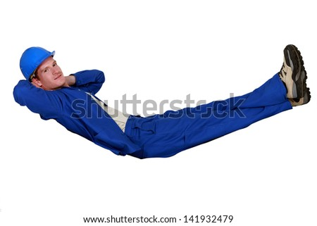 Construction worker lying in an imaginary hammock - stock photo