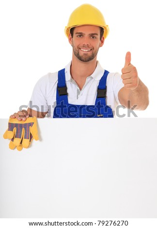 Construction worker making thumbs up while standing behind white wall. All on white background. - stock photo