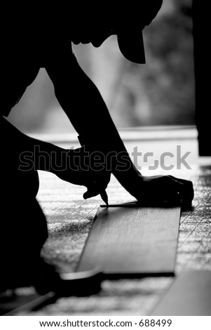 Construction worker measuring during a remodel and/or floor installation - black and white image. - stock photo