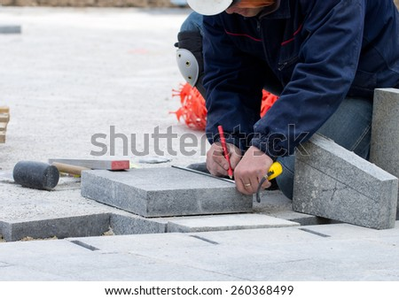 Construction worker measuring flagstone and preparing for cutting to fit in pavement - stock photo