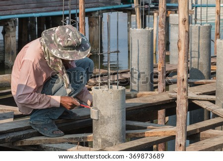 Construction worker measuring the pipe structure.