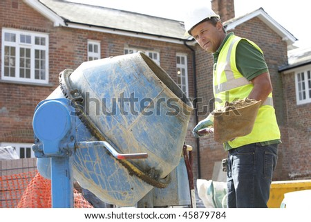Construction Worker Mixing Cement - stock photo