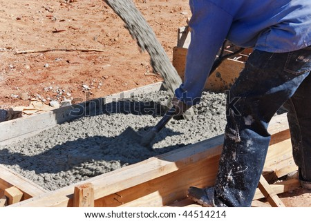 construction worker mixing concrete in the foundation with a shovel - stock photo