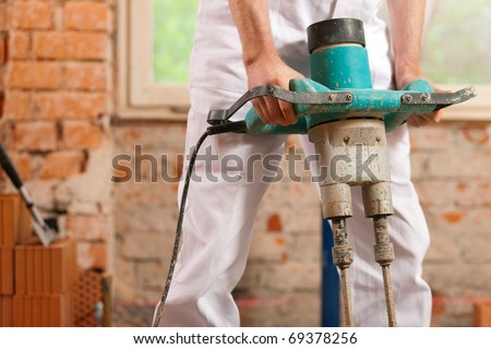 Construction worker mixing concrete or grout with a hand mixer - stock photo
