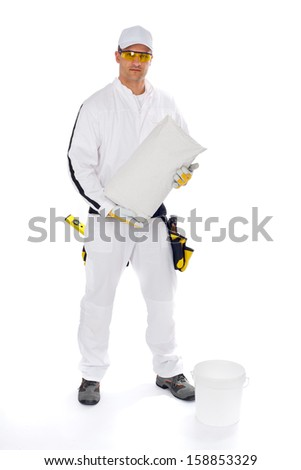 Construction worker mixing tile adhesive - stock photo