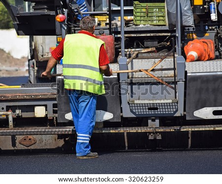 Construction worker next to an asphalt paving vehicle at the road construction - stock photo