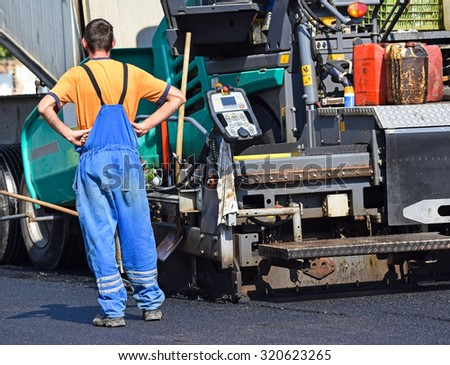 Construction worker next to an asphalt paving vehicle at the road construction