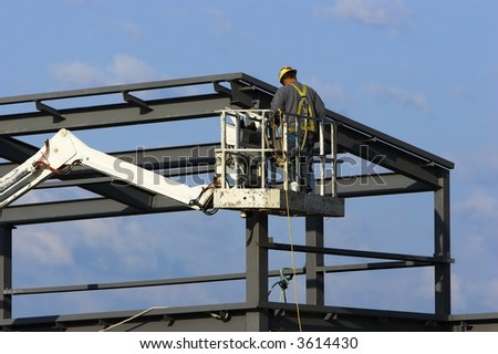 Construction worker on a cherry picker crane up at the roof of a high building - stock photo