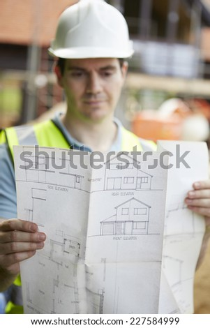 Construction Worker On Building Site Looking At House Plans - stock photo