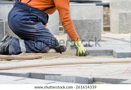 Construction worker on knees placing stone tiles in sand for pavement  - stock photo
