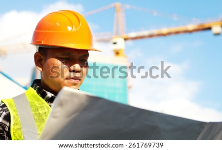 Construction worker on location site, looking blueprint with crane in the background - stock photo
