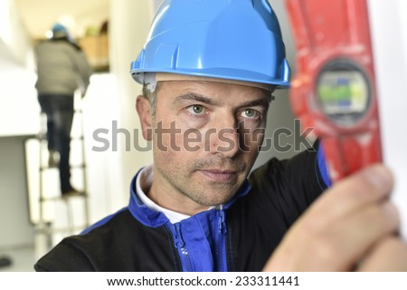 Construction worker on site using level
