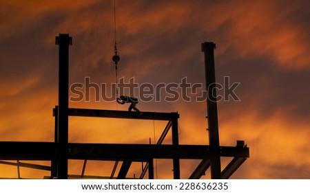 Construction worker on skyscraper - stock photo