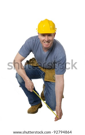 Construction worker on white background kneels and measures - stock photo