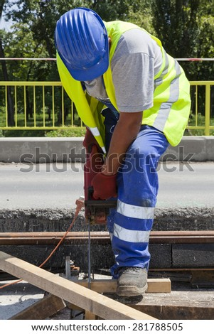 construction worker operating a chainsaw cutting wood - stock photo