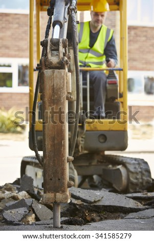 Construction Worker Operating Digger On Site - stock photo