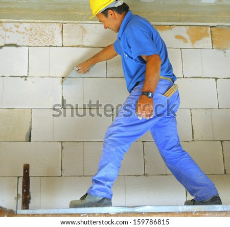construction worker performs an internal bricklayer wall - stock photo