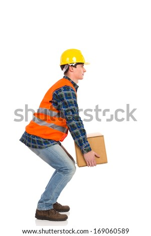 Construction worker picking up heavy box. Full length studio shot isolated on white. - stock photo