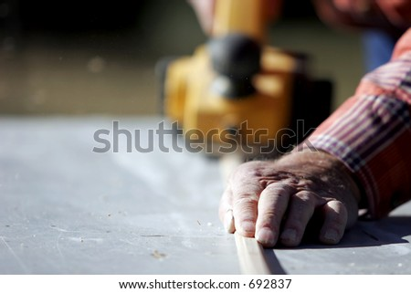 Construction worker planing a piece of wood for a building project. - stock photo
