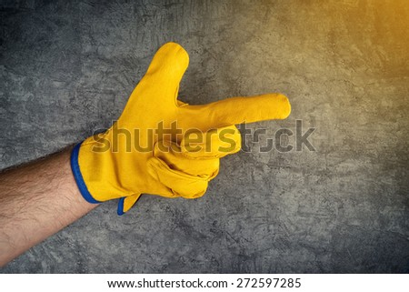 Construction Worker Pointing Finger at Something or Someone, Male Hand in Yellow Leather Protective Gloves. - stock photo
