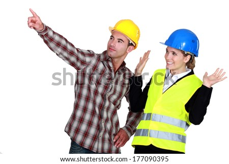 Construction worker pointing out a problem while his co-worker denies any involvement - stock photo