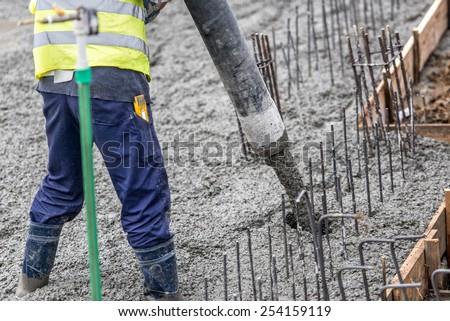 Construction worker pouring concrete, directing the pump tube - stock photo