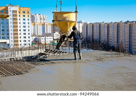 Construction worker pouring concrete during commercial concreting floors and building reinforced concrete structures - stock photo