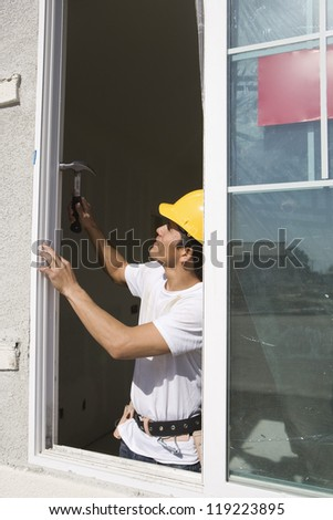 Construction worker preparing window frame - stock photo