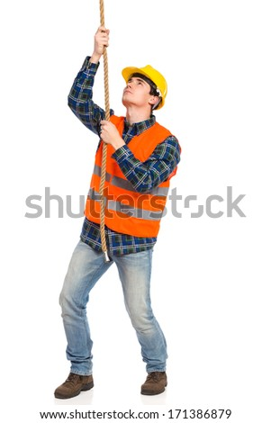 Construction worker pulling a rope. Full length studio shot isolated on white. - stock photo