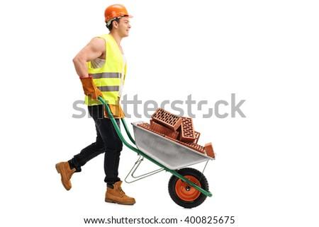 Construction worker pushing a wheelbarrow full of bricks isolated on white background - stock photo