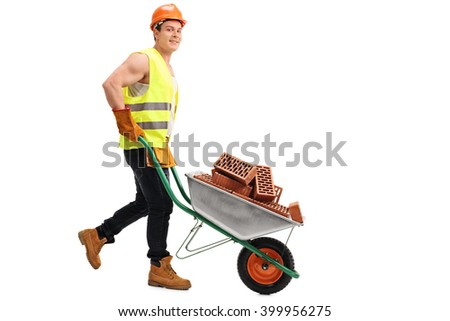 Construction worker pushing a wheelbarrow with a load of bricks in it and looking at the camera isolated on white background - stock photo