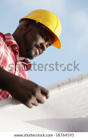 Construction worker reading plans outside - stock photo