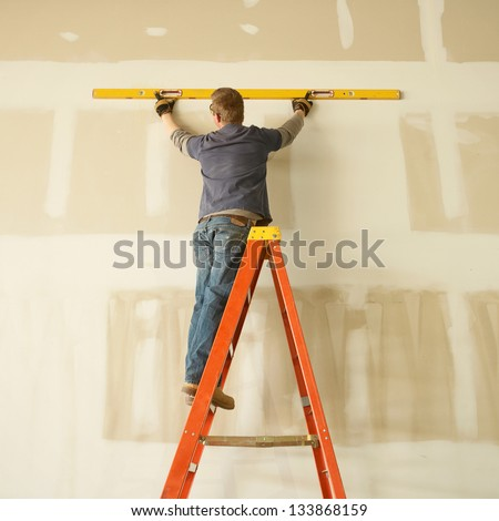 Construction worker remodeling home on ladder with level - stock photo