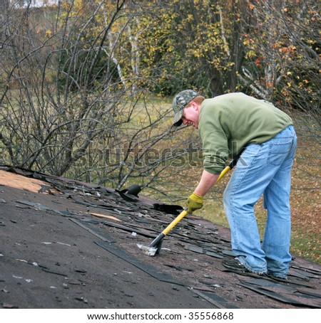 construction worker removes shingles from a roof