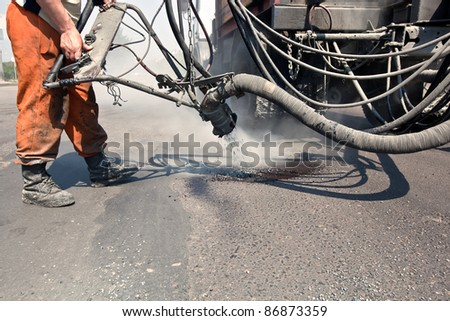 Construction worker repairing holes on the road with gravel and bitumen