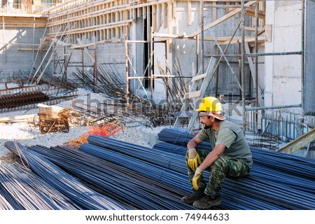 Construction worker resting on piles of reinforcement steel bars, in a busy construction site - stock photo